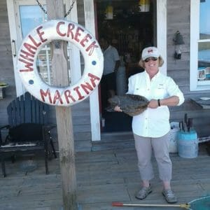 Karen Mitchell holding flounder catch on dock at Whale Creek Marina
